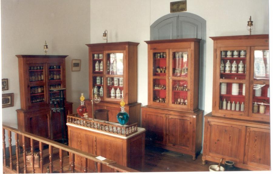Posicionamento da Farmácia Magalhães Gomes com extratos, tinturas e vidrarias na 1ª sala e sua reorganização na 2ª sala.